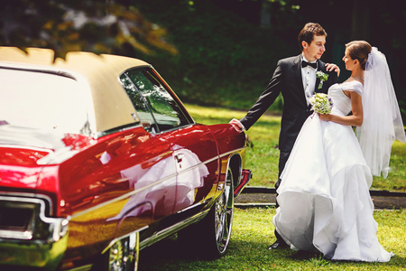 Groom leans on a old American car holding a bride Stock Photo