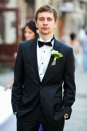 Groom stands proud holding hands in his pockets