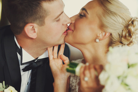 tenderly: Closeup of tenderly kissing wedding couple