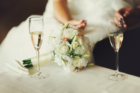 Two wineglasses with champagne stand on the table behind a wedding bouquet Stock Photo