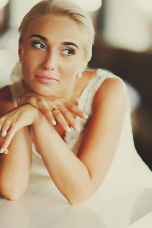 Pretty blond bride sits leaned on a piano holding her face with hands Stock Photo