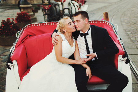 A wedding couple sit in the red open carriage
