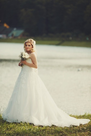 shiny day: Pretty blonde bride stands on the lake shore in a shiny day Stock Photo