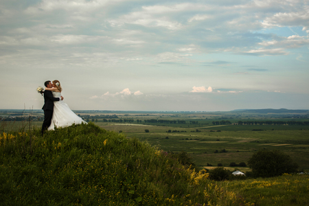 them: Bride kisses a groom standing on a hill with a great view on the fields behind them