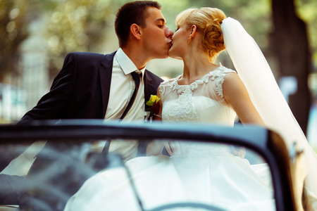 Fiance kisses pretty blonde bride sitting on a black cabriolet Stock Photo