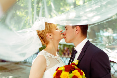 Groom touches brides chin tenderly standing under her veil