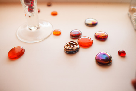 Wedding rings lie on  red decorative stones