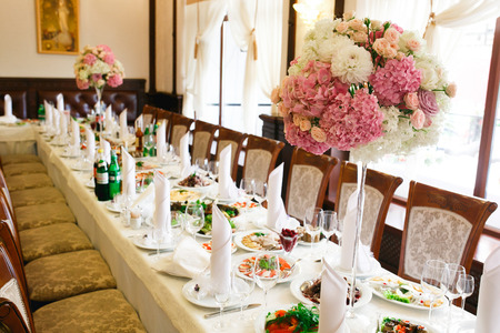 Long dinner table decorated with pink flowers in high vases Reklamní fotografie - 67796762