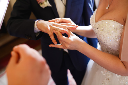 fingers put together: Bride puts a ring on grooms finger delicately