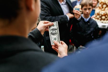 mam: Mam holds one hundred dollars in his hands