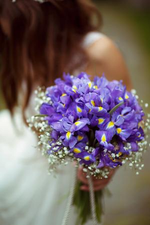 A bouqet of violet crocuses is held by a bride