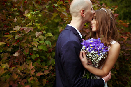 Bride hold a wedding bouqet behind her chest while groom kisses her forehead Stock Photo