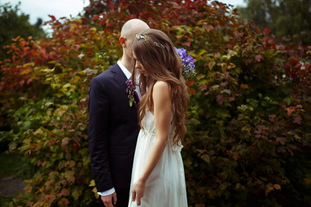 big behind: Tender bride stands behind a groom with closed eyes in the front of a big bush