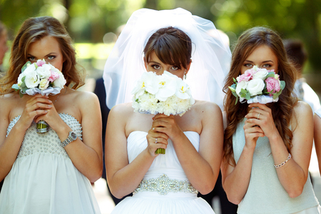 Bride and bridesmaids hide their faces behind little wedding bouqeuts