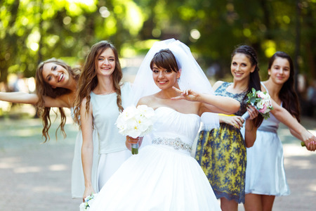 fiance: Bride rises the sign of virctory posing with pretty bridesmaids