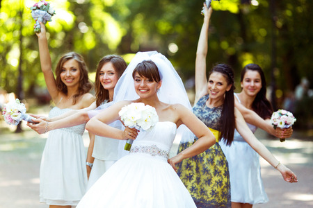 arm bouquet: Smiling bride with a bouquet in her arm poses with a girls in park