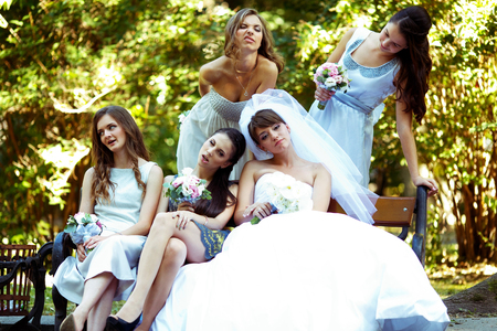 Bride and bridesmaids grimace sitting on the bench in park Stock Photo