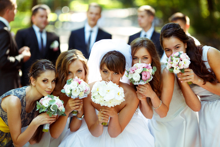 Girls and bride pose with wedding bouquets while groom and groomsmen stand on the background