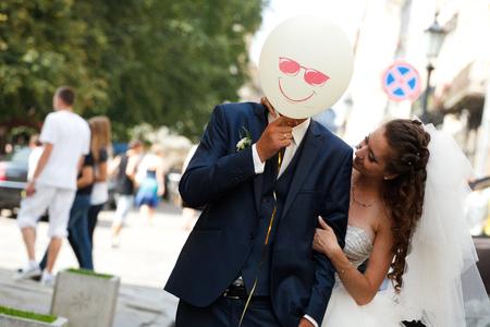 fiance: Groom has fun while hiding behind a smiling balloon