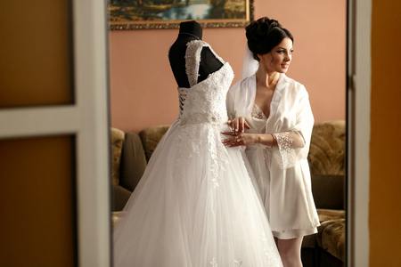 finery: The bride stands near wedding  dress in the room