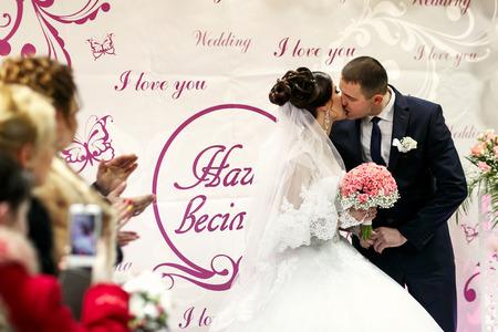 The brides kissing  near wedding banner