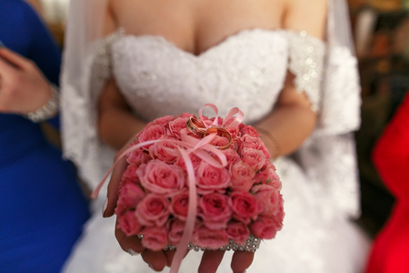 The bride keeps a bouquet with rings