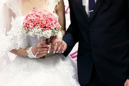 fiance: The brides hold hands near wedding banner