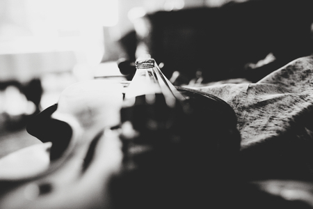 A black and white picture of wedding rings lying on the violin