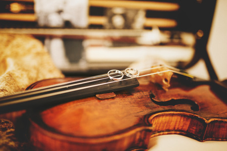 Sparkling wedding rings lie on the violin strings Stock Photo