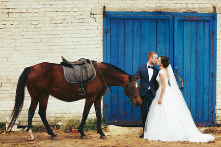 Bride and groom stand with a horse behind blue gates