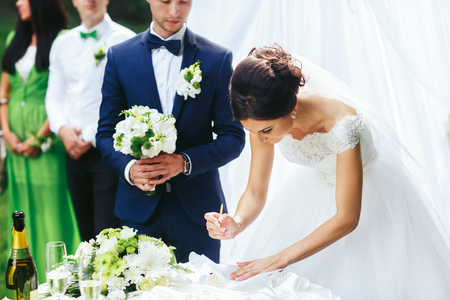 fiance: Bride signs an engagement paper standing behind a groom