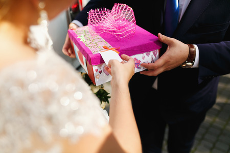 Man holds a pink present box