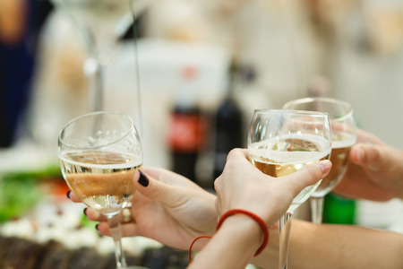 People cheers with glasses full of white wine Stock Photo