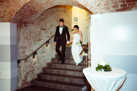 Bride and groom walk downstairs into the restauant holding their hands together Stock Photo