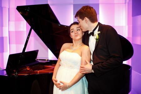 彼女は彼女の妊娠中の腹を保持している間に新郎が花嫁をキスします。 写真素材 - 70024977