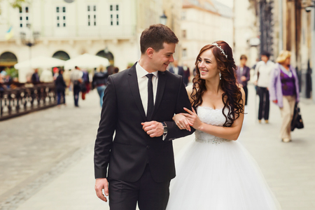 Groom leads a bride along the street holding her hand Stock Photo