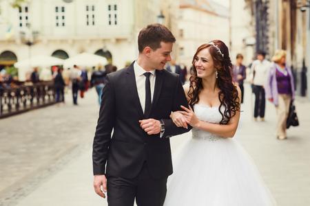 Groom leads a bride along the street holding her hand 版權商用圖片