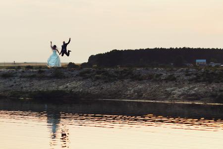 Gli sposi novelli felici saltano sulla riva del lago