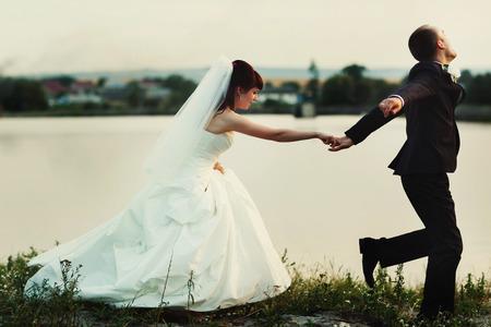 Groom runs along the lakes shore holding brides hand tightly Stock Photo