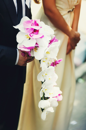 Man holds a bouqet made of white orchids