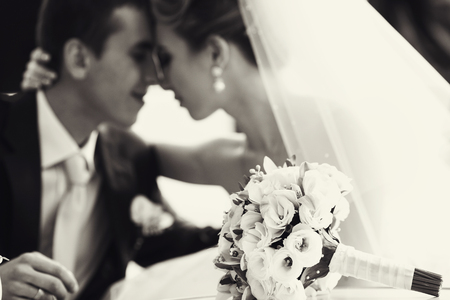 peacefull: Wedding bouquet lies on the table before peacefull newlyweds