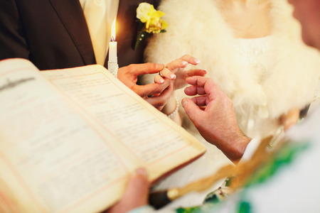 christian marriage: Groom puts a wedding ring on delicate brides finger standing in the church Stock Photo