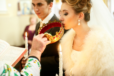 Bride kisses a golden crown held by a priest during the ceremony