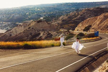 vestidos de epoca: Happy wedding couple walks along the highway