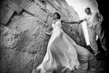 Wind blows brides dress while she goes downstairs with a groom