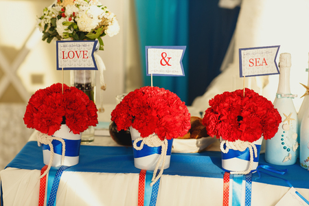 mixed marriage: Flags with lettering Love & sea stand in a bouquets of carnations