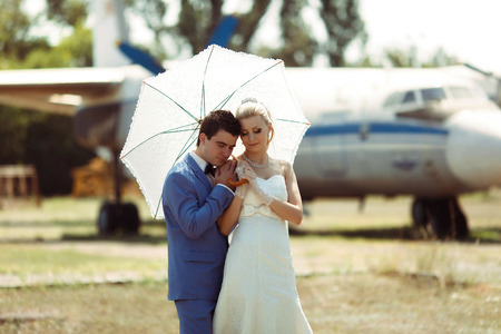 embracement: Groom and a bride with an umbrella in the wedding day