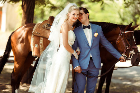 embracement: Joyful bride and a groom next to a horse
