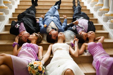Novia y el novio con los amigos en las escaleras