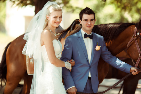 embracement: Smile of the bride next to a groom and a horse